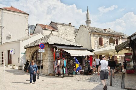 Mostar, Bosnia and Herzegovina - September 15, 2018: Old Town. You can see the architecture typical of the region, numerous souvenir and regional products shops . Tourists are walking along the street
