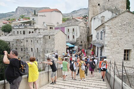 Mostar, Bosnia and Herzegovina - September 15, 2018: view from the Old Bridge to the Old Town, You can see the generic architecture. Many tourists are on the bridge and on the street.