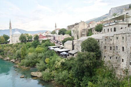 Mostar, Bosnia and Herzegovina - September 15, 2018: the bank of the Neretva River. A fragment of the old town and towers of minarets are visible. You can see numerous tourists on the street and river