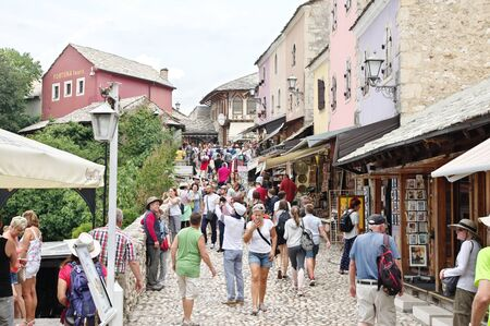 Mostar, Bosnia and Herzegovina - September 15, 2018: cobbled street in the center of the Old Town. You can see the architecture typical of the region, numerous shops with souvenirs and regional handic