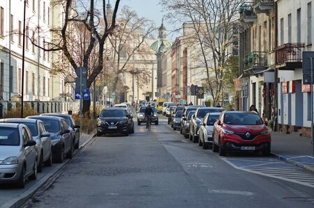 Cracow, Poland – November 07, 2018: Rajska street. Along the street there are historic tenement houses and parked cars. In the background you can see the church of the Carmelite Fathers.