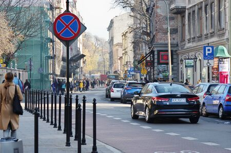 Cracow, Poland – November 07, 2018: Krupnicza street. Along the street there are historic tenement houses and parked cars. You can see many pedestrians, shops, pubs and small construction machi