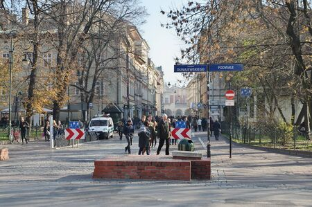 Cracow, Poland – November 07, 2018: Szewska street. In the front you can see a fragment of Planty Park, in the background you can see the Cloth Hall. There are many pedestrians on the street.