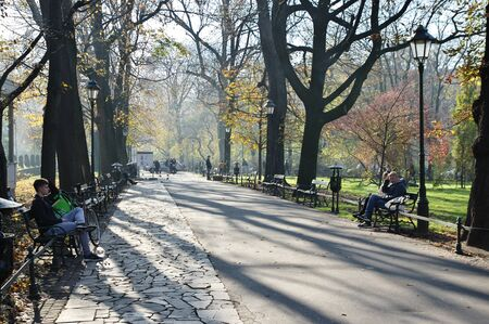 Cracow, Poland – November 07, 2018: Cracow, Poland – November 07, 2018: Autumn in Planty Park, which surrounds the Old Town. You can see trees in autumn colors and people resting on benc 에디토리얼
