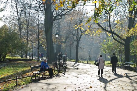 Cracow, Poland – November 07, 2018: Autumn in Planty Park, which surrounds the Old Town. You can see trees in autumn colors and people resting on benches or walking. 에디토리얼