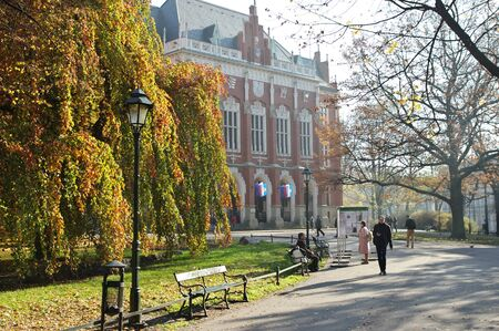 Cracow, Poland – November 07, 2018: Autumn in Planty Park, which surrounds the Old Town. You can see trees in autumn colors and people resting on benches or walking. In the background you can see Collegium Nowum of the Jagiellonian University. 新聞圖片