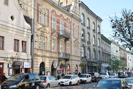 Cracow, Poland – November 07, 2018: Karmelicka street. Along the street there are historic tenement houses and parked cars. You can see some pedestrians, shops and pubs.