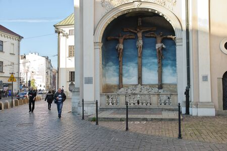 Cracow, Poland – November 07, 2018: Karmelicka Street. On the right, there is a fragment of the southern wall of the Carmelite church. In the niche of the wall there is a complex of three sculptures