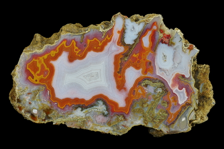 A cross-section of agate. Multicolored silica rings colored with metal oxides are visible. In the center a snow-white chalcedony is interwoven with gray, transparent quartz. Origin: Agouin, Atlas mountains, Morocco.