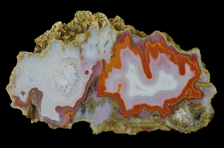 A cross-section of agate. Multicolored silica bands colored with metal oxides are visible. . Chalcedony lamination occurs in some places, highlighted with a purple pigment. Origin: Agouin, Atlas mountains, Morocco.