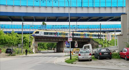 Krakow, Poland – May 12, 2019: district of Podgórze, Dąbrowskiego street. You can see parked cars and the railway viaducts. There is a train on one viaduct.