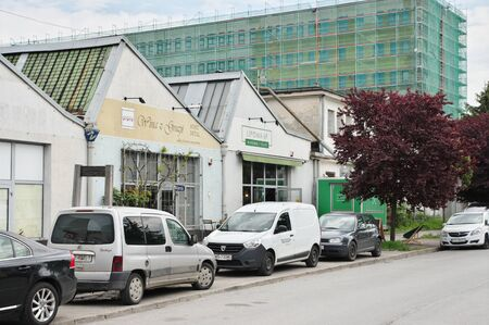 Krakow, Poland – May 12, 2019: district of Podgórze, Lipowa street. Old industrial buildings adapted for shops and pubs. In the background you can see an old office building that is being re