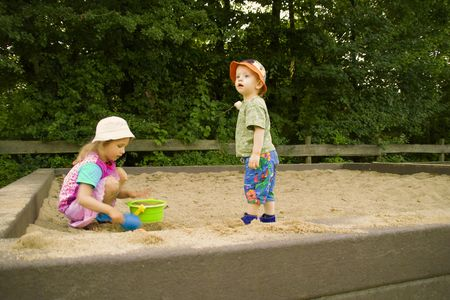 The boy and the girl play a sandbox