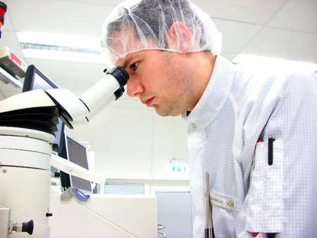 The men looks in stereomicroscope eyepieces Stock Photo - 8392207