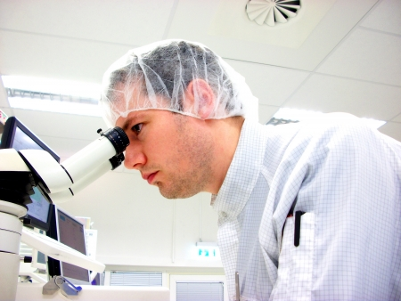 The men looks in stereomicroscope eyepieces Stock Photo