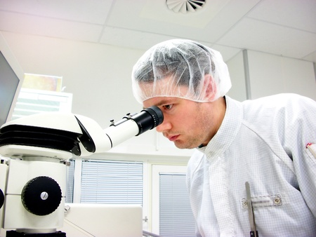 The men looks in stereomicroscope eyepieces photo
