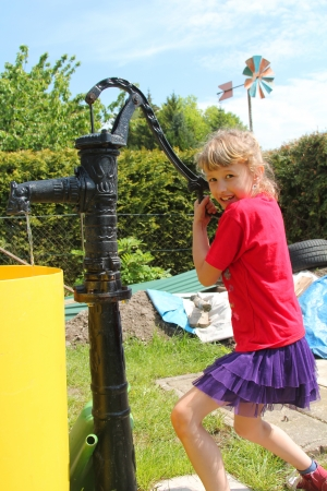 The girl works at the water pump photo