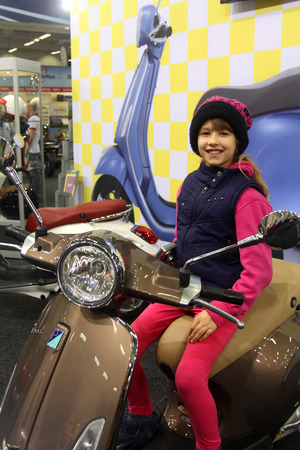 tage: HAMBURG, GERMANY - FEBRUARY 22: The girl with the motorscooter on February 22, 2014 at HMT (Hamburger Motorrad Tage) expo, Hamburg, Germany. HMT is a large motorcycle expo