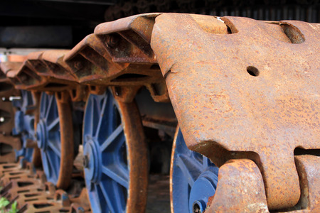 The old rusty caterpillar of the crawler tractor