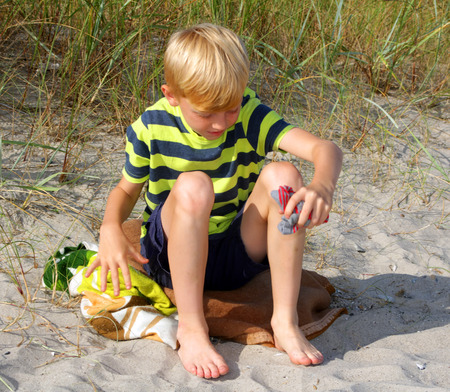 A teenage boy sits on the sand. Stock Photo