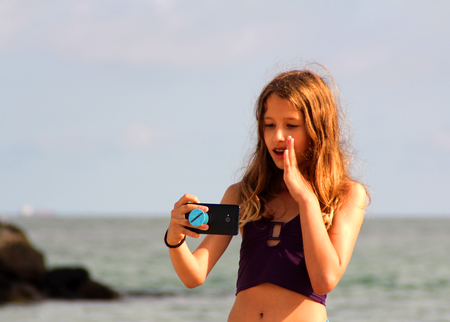 The teenage girl make a selfie on the sea beach.