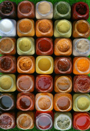 Some small jars with various samples of sauces and marinades on a white background