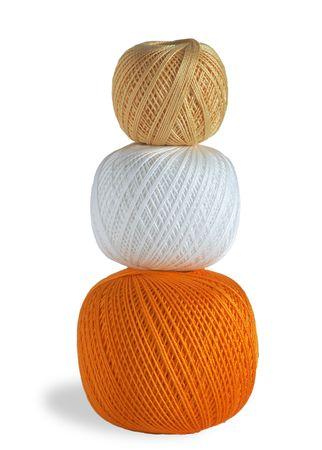 Three woolen balls, white, orange, beige, on a white background