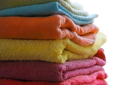 Stack of coloured towels on the white background, isolated