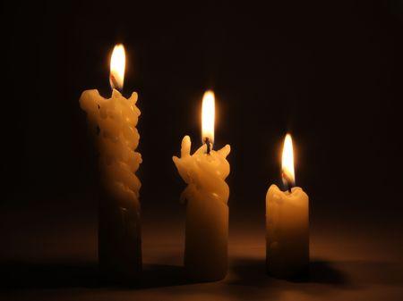 Three burning candles in dark