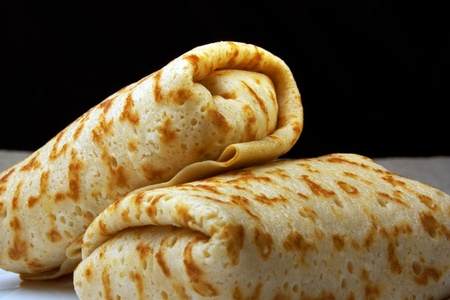 Pancakes with rolled up into a roll, folded in envelope, on a black
