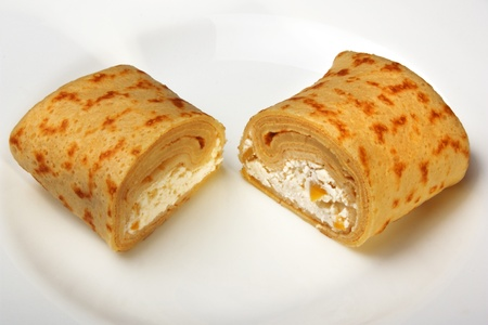 Pancakes with cottage cheese and dried apricots, rolled into rolls cut in half