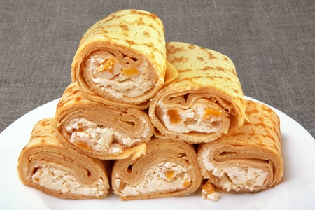 Pancakes with cottage cheese and dried apricots, rolled into rolls