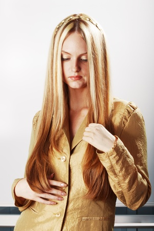 girl with long hair in a suit of gold cloth Stock Photo