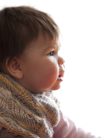 rosy-cheeked baby in a knitted sweater stares in front of him, opened his mouth