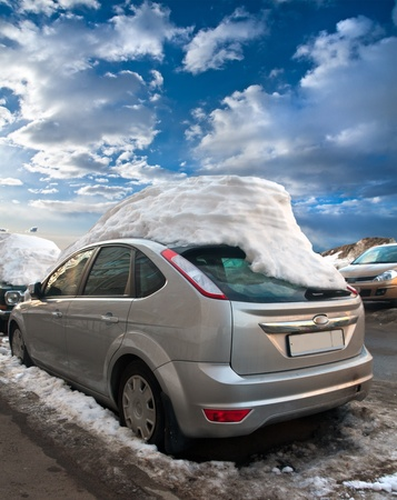 car under the snow cap on the street in the spring photo
