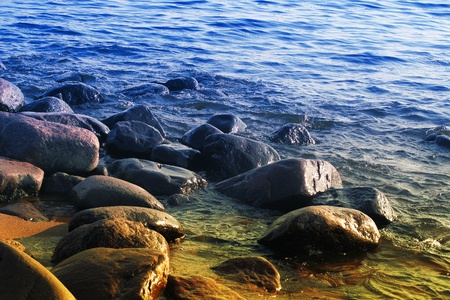 granite boulders on the shore of the water at sunset