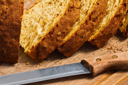 bread crumbs, a knife and a few loaves of fresh bread with a crispy crust on a wooden board
