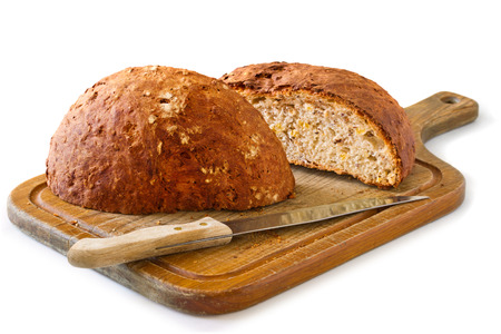 round rye bread, cut in half, lying with a knife on a wooden board Stock Photo