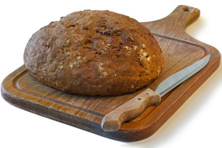 knife and a loaf of fresh bread with a crispy crust on a wooden board