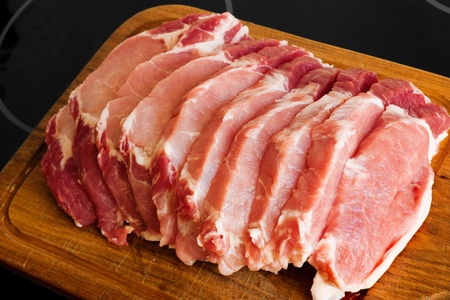 slices of fresh pork meat with a bone on a wooden cutting board Stock Photo