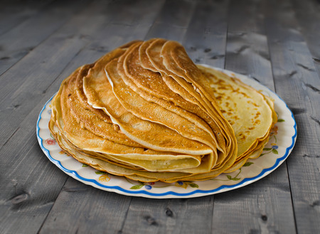 pile of pancakes on the plate on the old wooden table