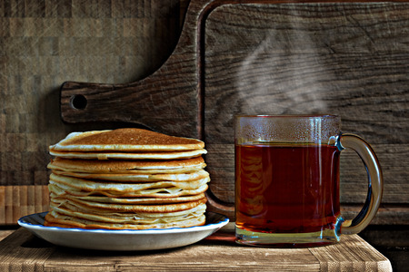 breakfast consisting of a stack of pancakes and a glass cup with tea on a wooden board