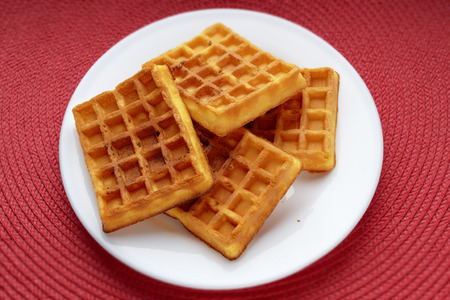freshly baked Belgian waffles in a white plate on a red