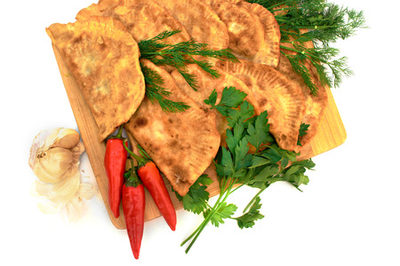 pastries of thin unleavened dough stuffed with meat and hot spices on a wooden deck with dill and pepper