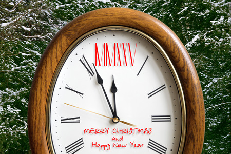 number 12: new year clock with 2015 instead of the number 12 (Roman numerals) on the background of snow-covered fir trees