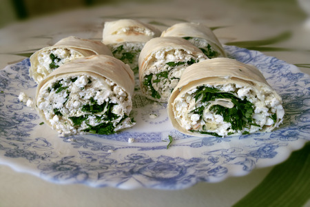 lavash rolls with curd cheese and herbs on the plate