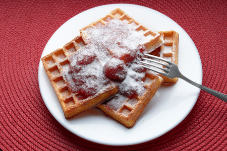 freshly baked Belgian waffles with strawberry jam in a white plate with a metal fork on a red table