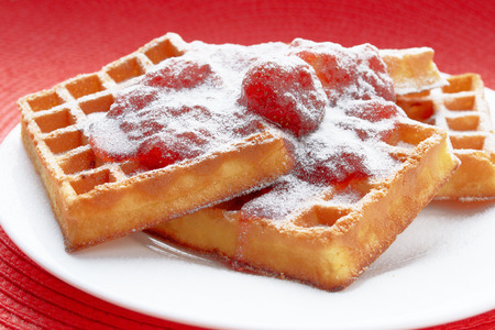 freshly baked Belgian waffles with strawberry jam in a white plate on a red table Stock Photo