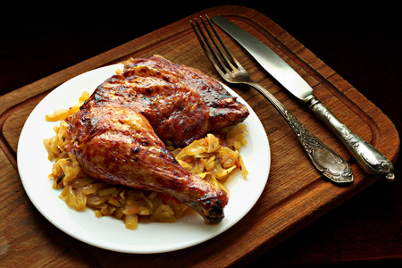 grilled chicken with cabbage on a plate near a knife and fork on a wooden board Stock Photo