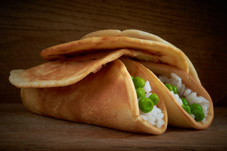 pancakes with rice and green peas lie on a wooden board